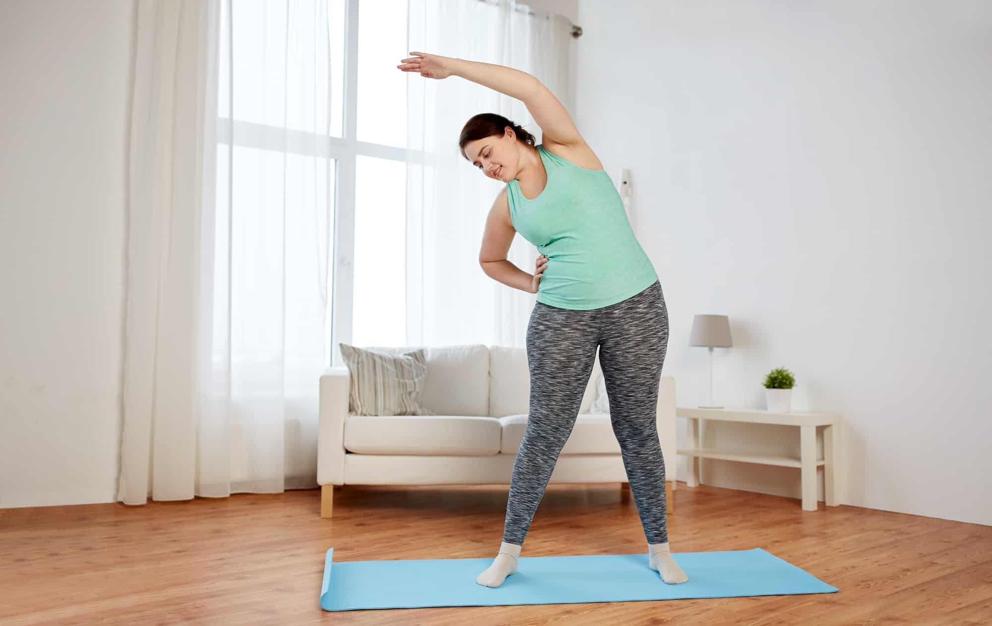 plus size woman exercising on mat at home