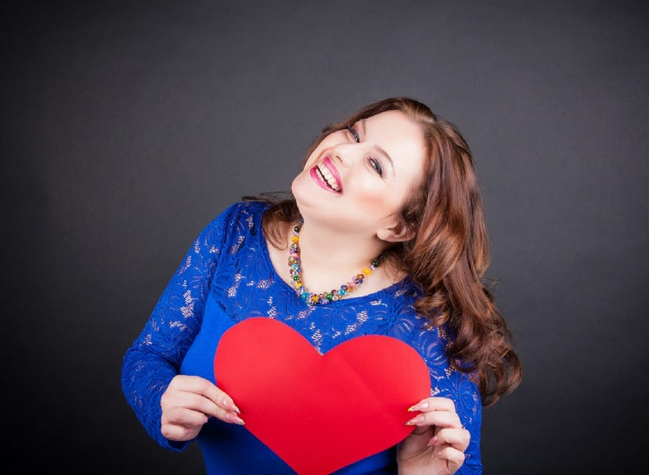 happy plus size woman holding a red heart