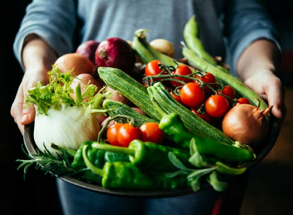 Plus Size woman holding a big bowl full of colorful vegetables