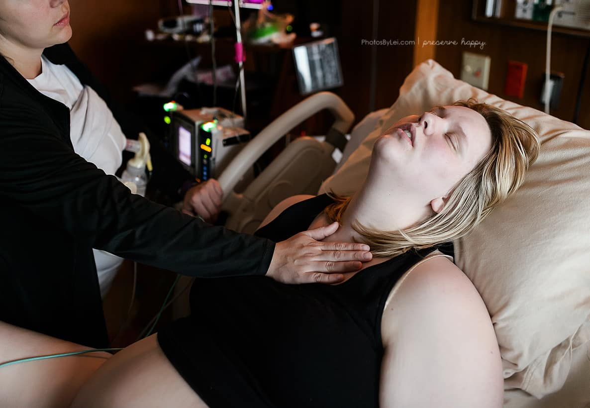 woman leading back in bed while giving birth