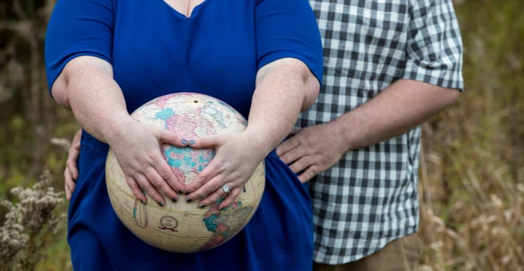 woman holding a globe to her belly for adoption photos