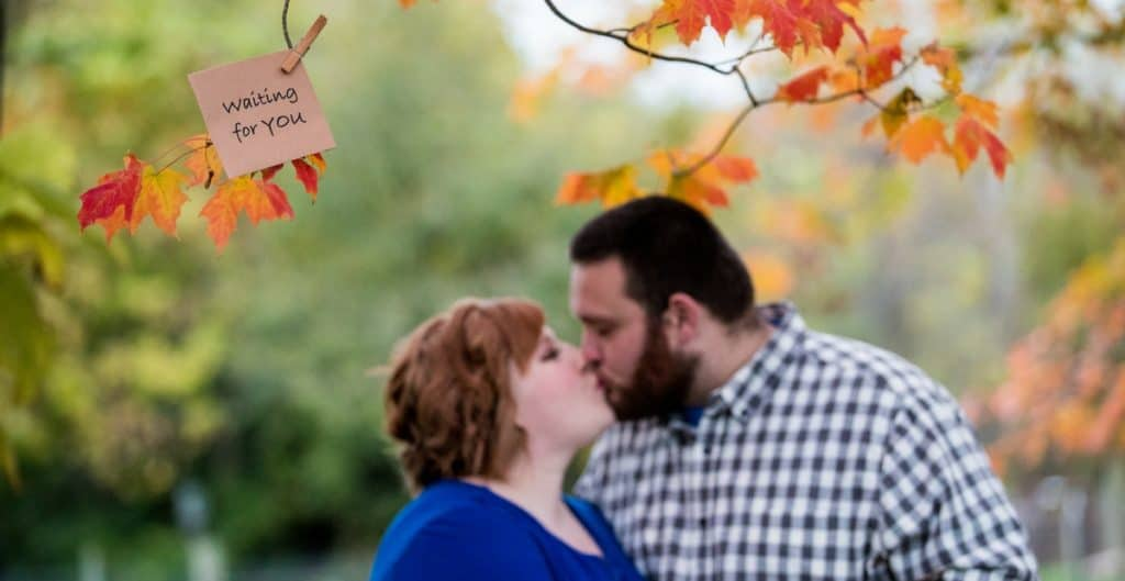 couple kissing taking adoption maternity photos