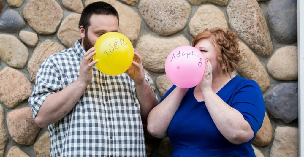 Maternity Adoption Photo Shoot with a couple blowing up balloons that say we're adopting
