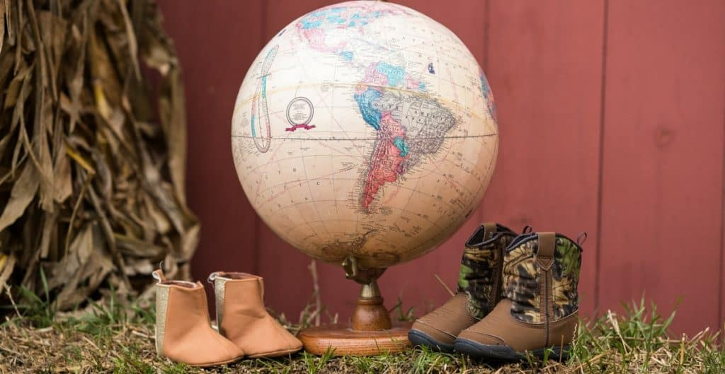 Adoption photos with a globe and baby shoes
