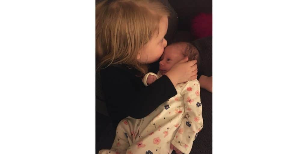sister kissing newborn baby sister