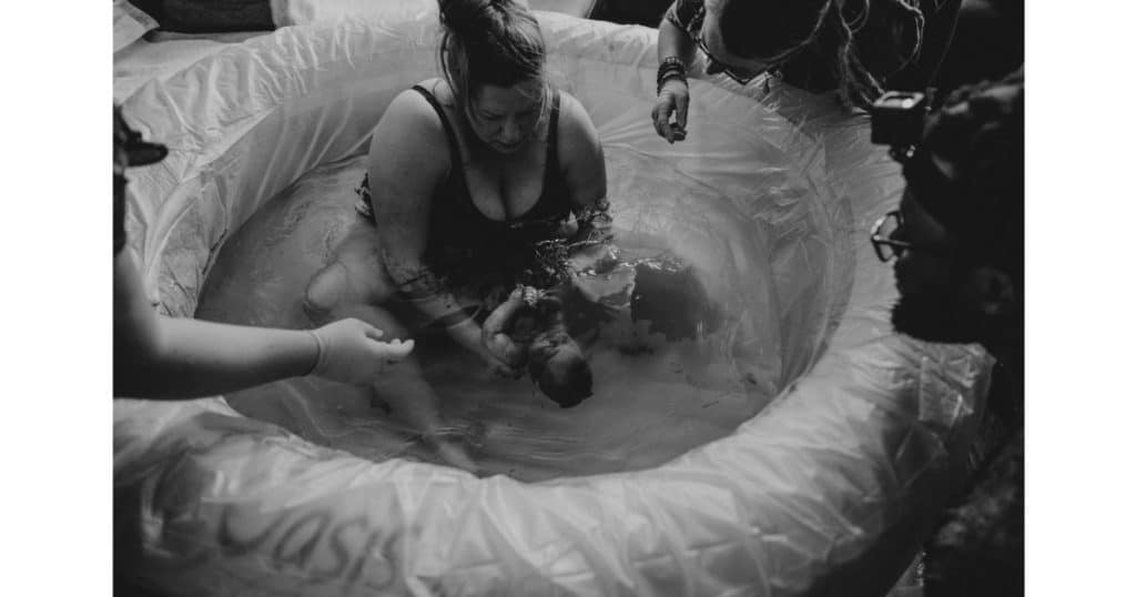plus size woman having a water birth holding baby