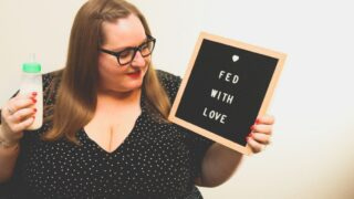 plus size mother holding bottle and Fed With Love sign