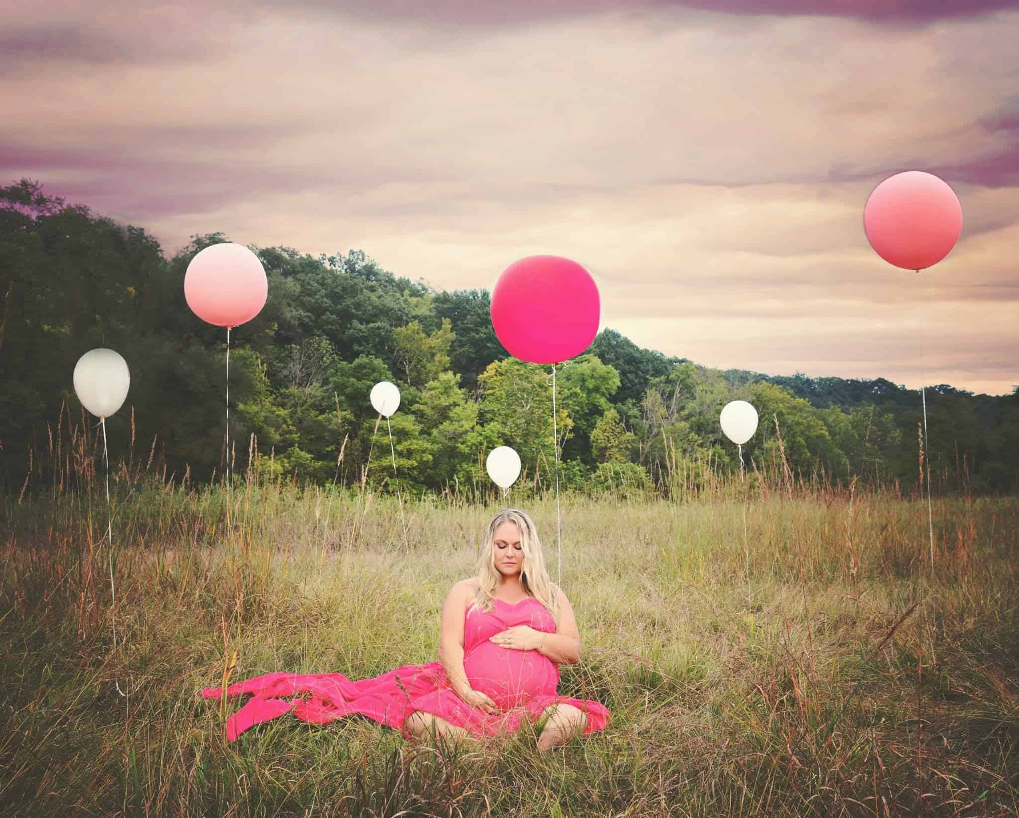 plus size maternity photo pink dress in field with balloons