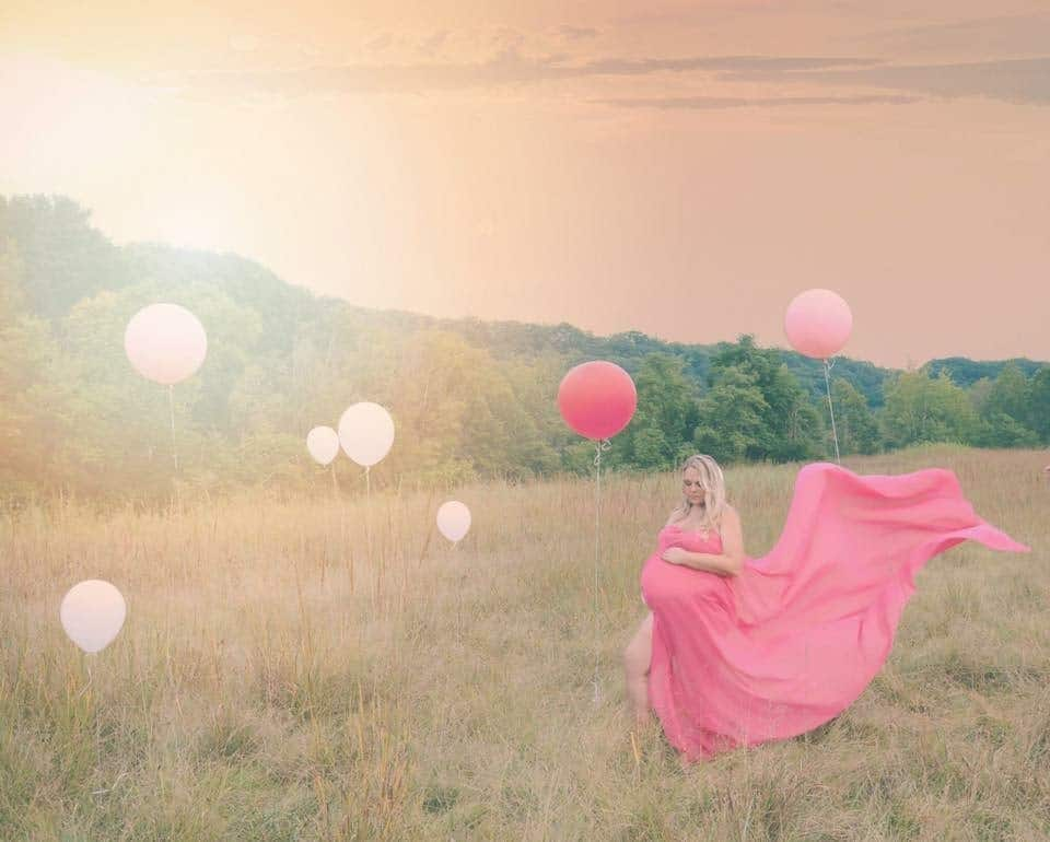 plus size pregnant woman in field with balloons