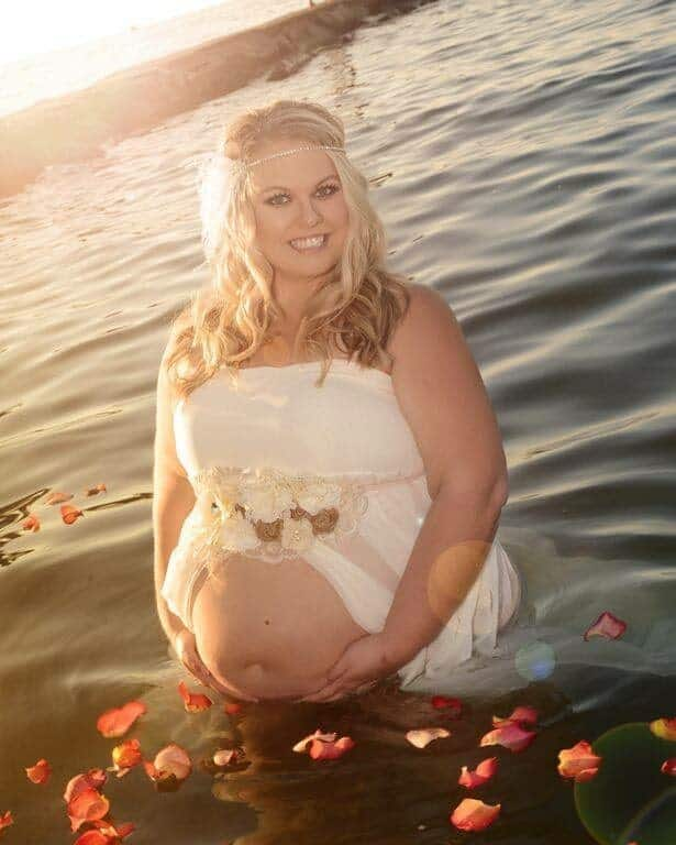 plus size pregnant woman standing in lake