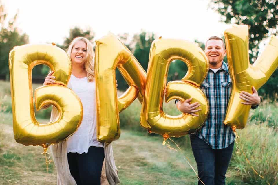 closeup of plus size maternity photo with balloons spelling out baby