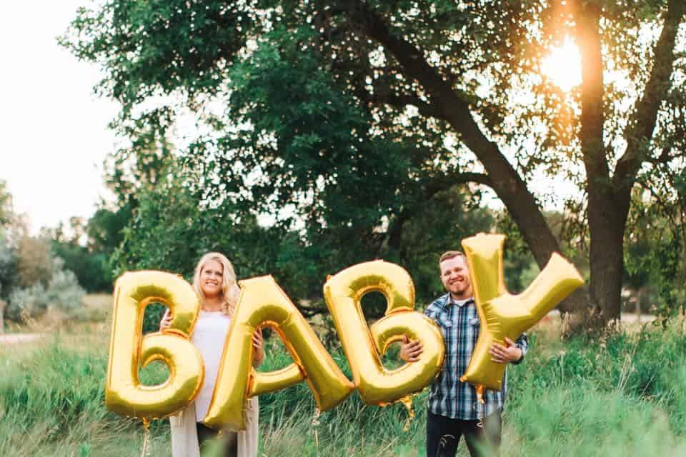 plus size maternity photo with balloons spelling out baby