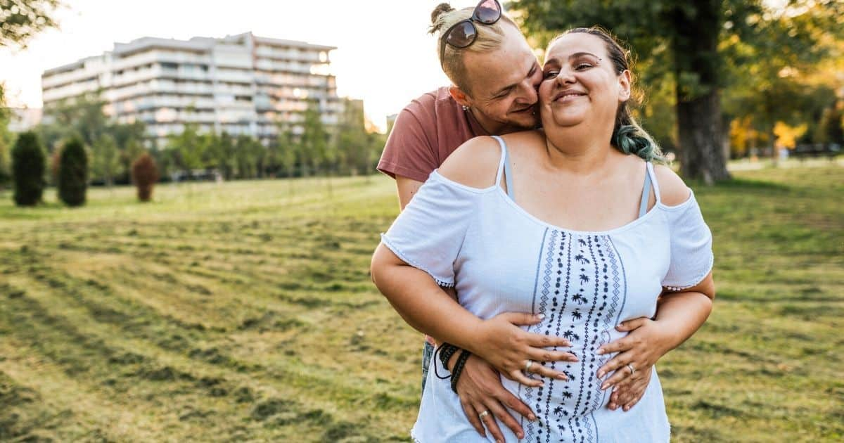 plus size woman who is plus size and pregnant with her husband at a park