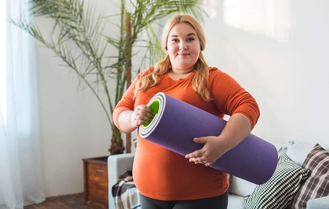 plus size woman holding yoga mat doing Pregnancy Exercises at Home